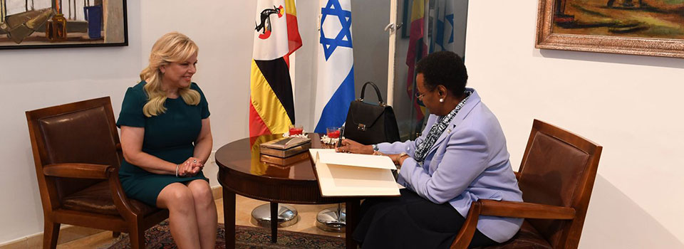 First Lady Janet Museveni signs a Visitors' book  on arrival at the Israel Prime Minister's residence in Jerusalem while Mrs Sara Netanyahu looks on