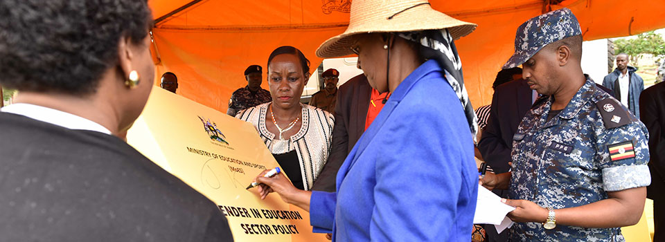 First Lady signs a dummy of the Ministry of Education and Sports Gender in Education Policy at its launch during the International Day of the Girl Child in Kyenjojo while the Youth and Children Affairs State Minister looks on.