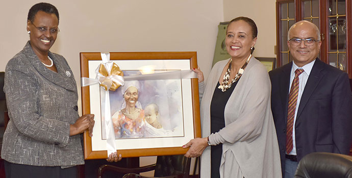 First Lady and Minister of Education and Sports Mrs. Janet Museveni hands over a gift to Ida Girma the out-going UNICEF Representative who was bidding farewell, while UNICEF's Chief Of Education Nebendra Dhal looks on at State House Nakasero on Monday.