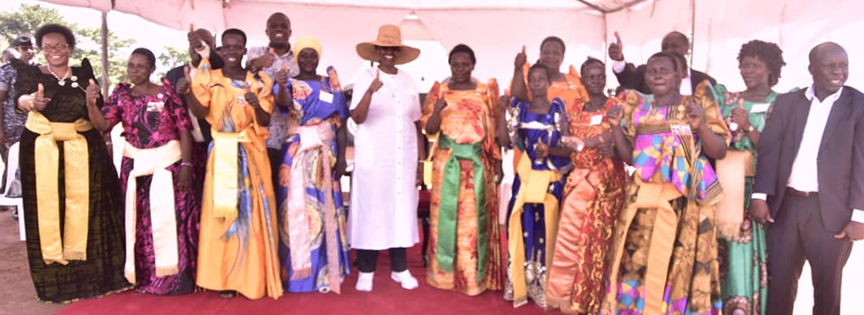 First Lady in white attire with a hat together with Hon Jennifer Namuyangu (on her left) and Hon Persis Namuganza (extreme left) pose with some of the Women Group Leaders from Kabweri Subcounty Kibuku District after the groups were commissioned on Saturday.